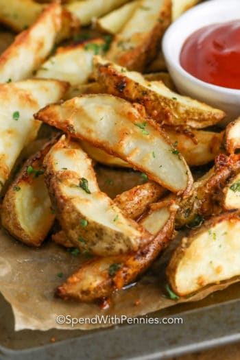 Crispy baked potato wedges on a sheet pan garnish with parsley with ketchup on the side