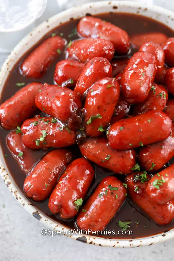 A bowl full of little smokies in sauce garnished with parsley.