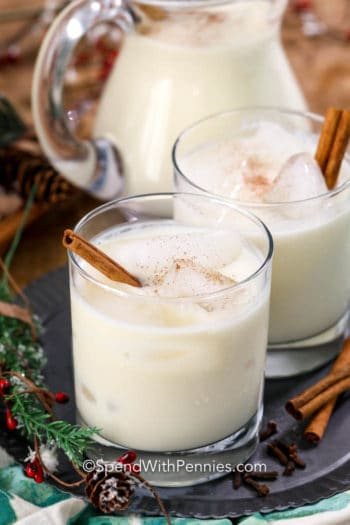 Homemade eggnog into glasses with cinnamon sticks and a pitcher in the background