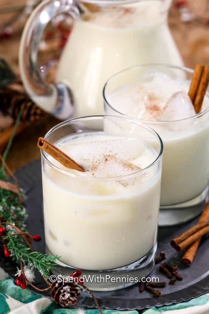 Two glasses of eggnog served on ice with cinnamon sticks and sprinkled with cinnamon.