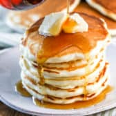 Pancakes on a plate with syrup being poured on