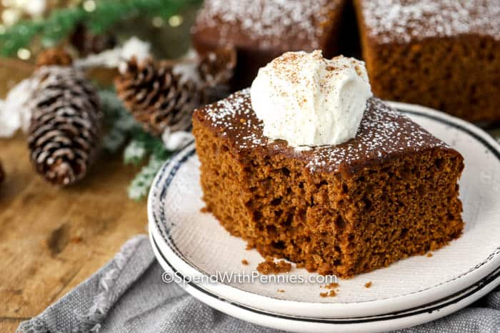 Piece of gingerbread on a plate with whipped cream