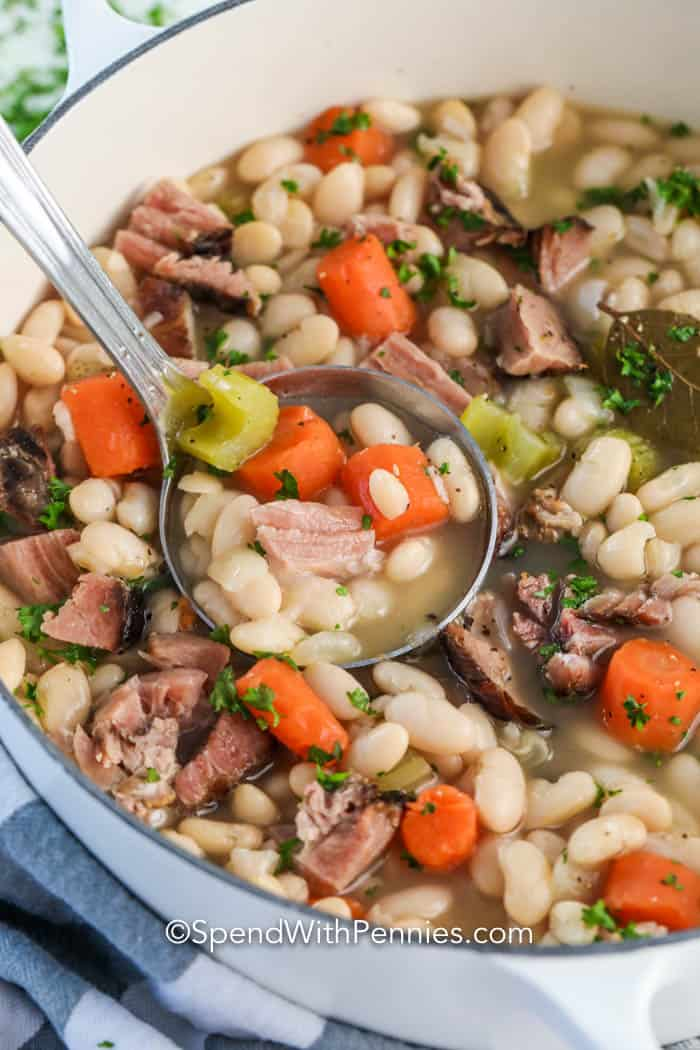 Great Northern beans and ham in a pot with some being scooped out with a ladle