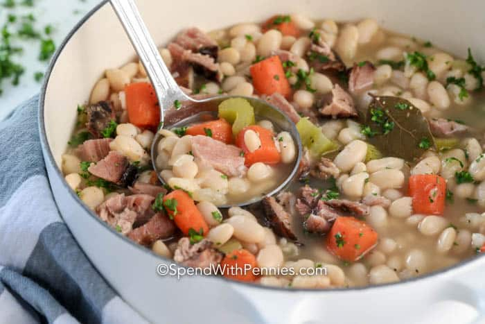 Great Northern beans and ham in a pot with a ladle
