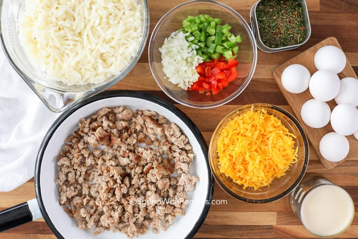 Ingredients for hash brown breakfast casserole in bowls on a wooden board