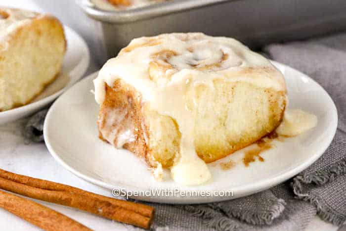 Homemade cinnamon roll on a white plate with icing