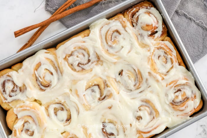Homemade cinnamon rolls in a pan with cinnamon sticks on the side