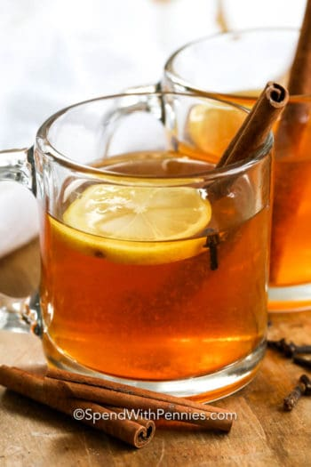 Hot toddy in a clear mug with cinnamon sticks and lemon slices