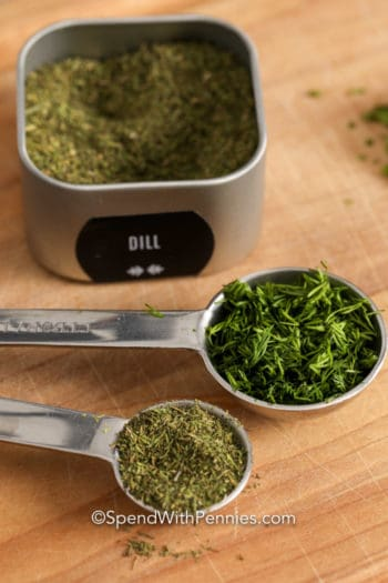 Herbs in measuring spoons and in a container on a wooden board