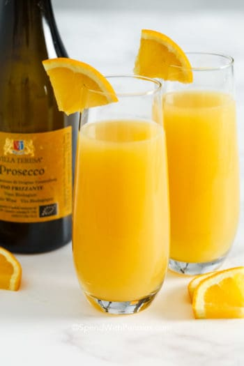 Two mimosas in glasses with orange slices