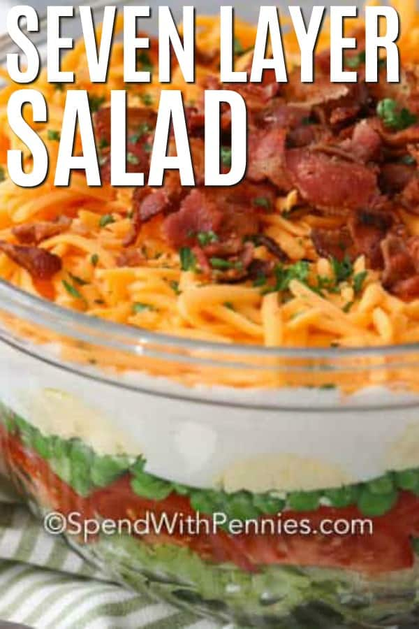 A glass bowl of layered salad topped with bacon and cheese