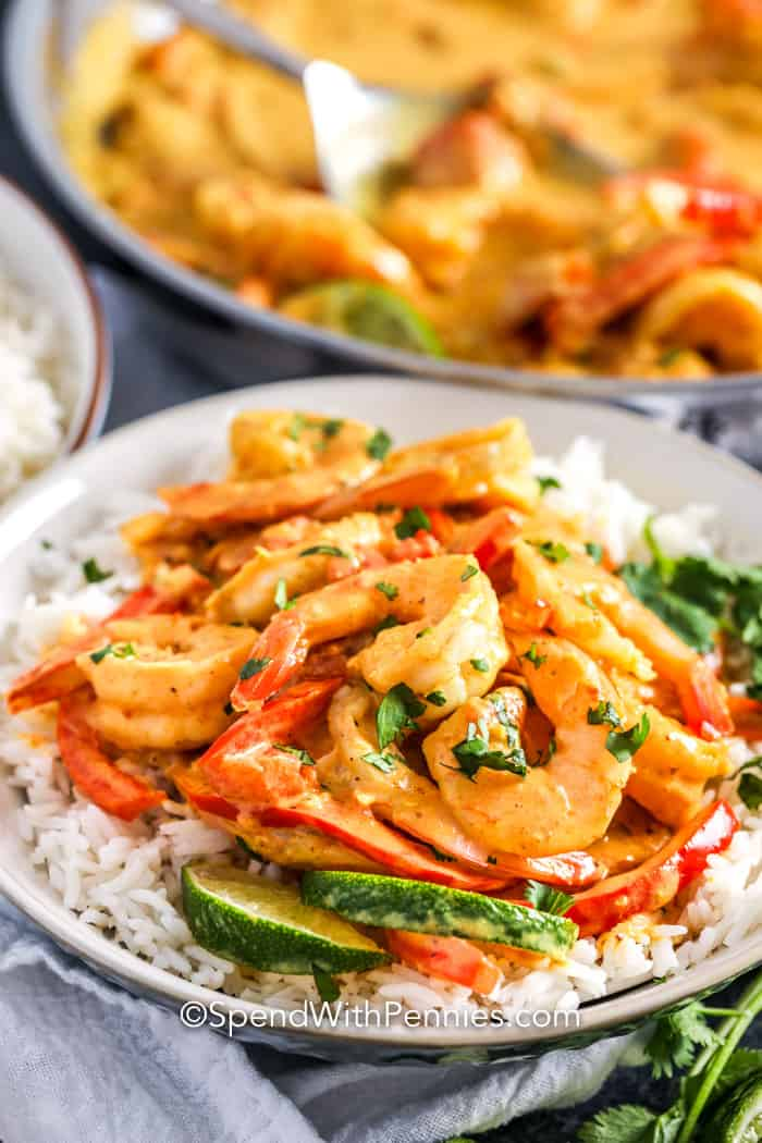 A serving of shrimp curry served over rice with lime slices.