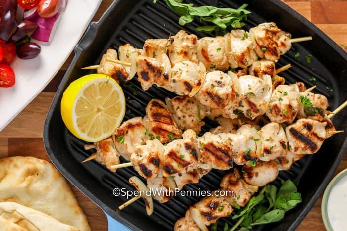 Chicken Souvlaki on a grill plate with half a lemon.