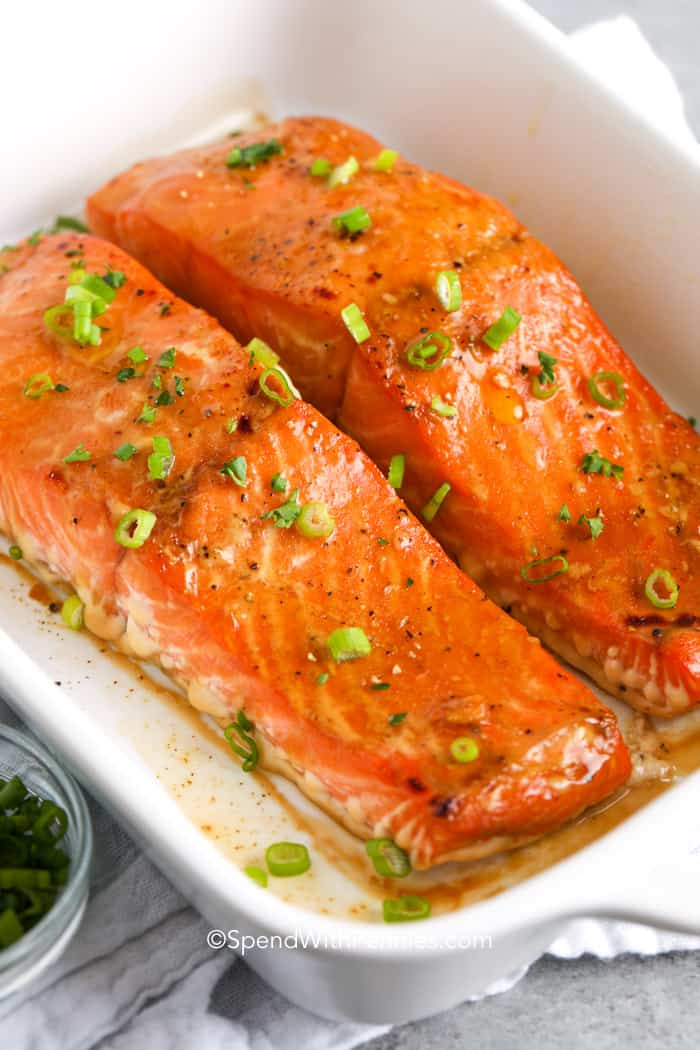 Baked salmon filets in a dish topped with green onions