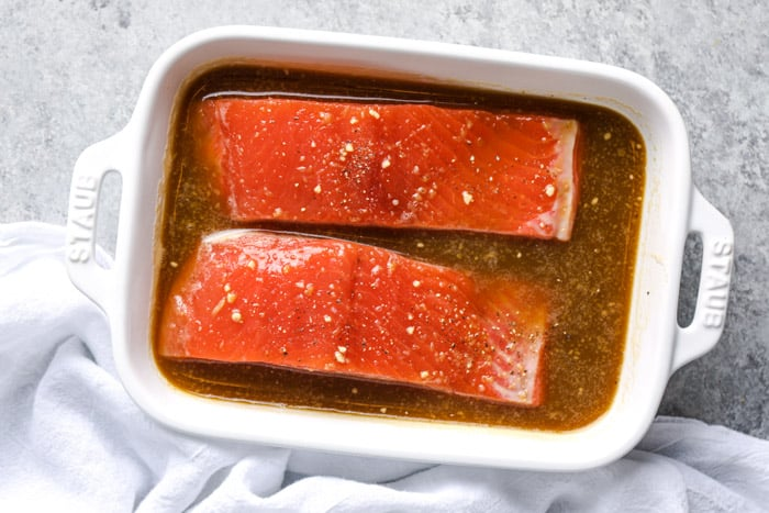 Baked salmon filets being marinated in a soy orange marinade