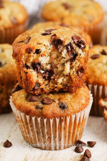 Banana Chocolate Chip Muffin with a bite taken from it with muffins behind