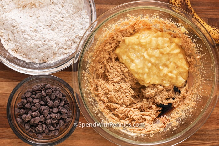 Overhead shot of ingredients for Banana Cookies; bowl of flour, bowl of chocolate chips, bowl with wet ingredients.