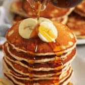 Banana Pancakes with bananas and syrup being poured on