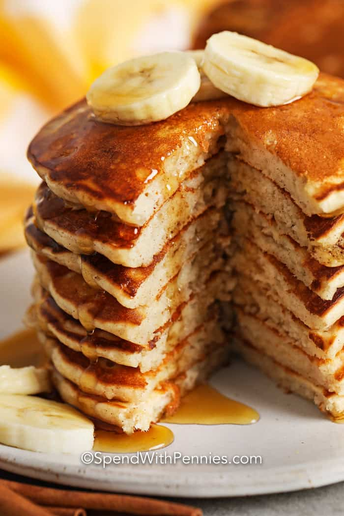Close up of Banana pancakes sliced, with bananas and syrup on top.
