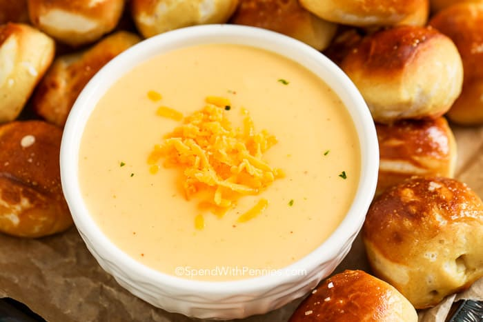 Beer cheese dip in a bowl topped with cheddar cheese and surrounded with soft pretzel bites