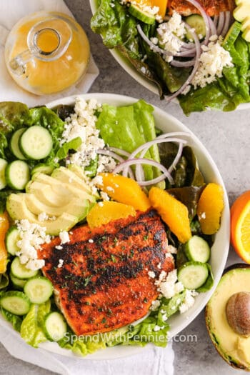 huge bowl of Blackened Salmon Salad with dressing and ingredients beside