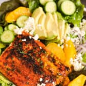 Blackened Salmon Salad in a bowl with dressing