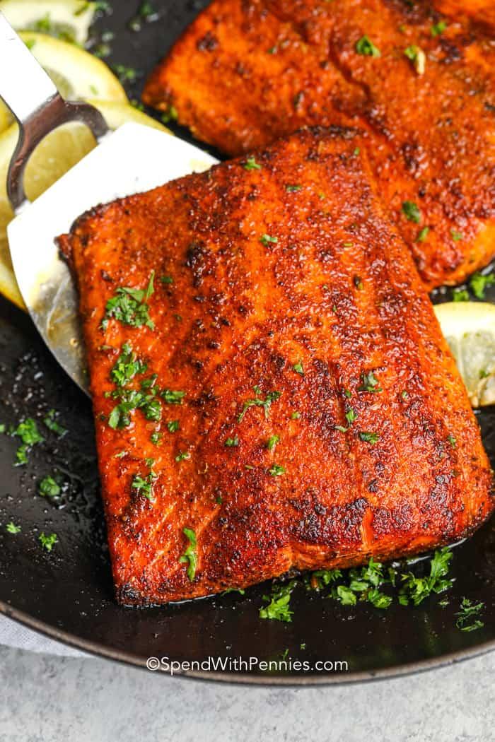 a spatula lifting blackened salmon from cast iron