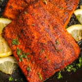 two pieces of cooked blackened salmon topped with parsley and served with lemons