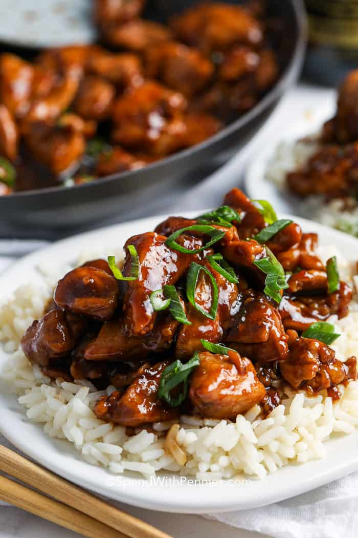 Bourbon Chicken on a plate with rice, garnished with green onion.