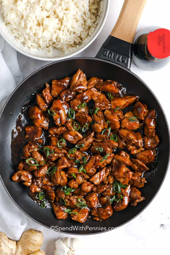 Close up of Bourbon Chicken in a pan, garnished with green onion.