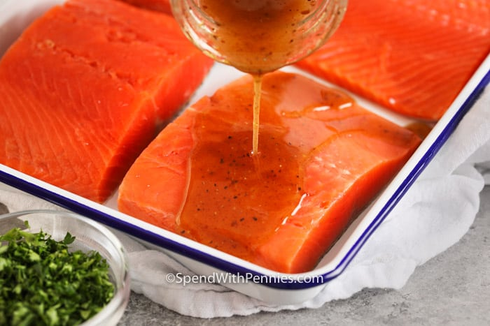 Salmon marinade being poured over a fillet.