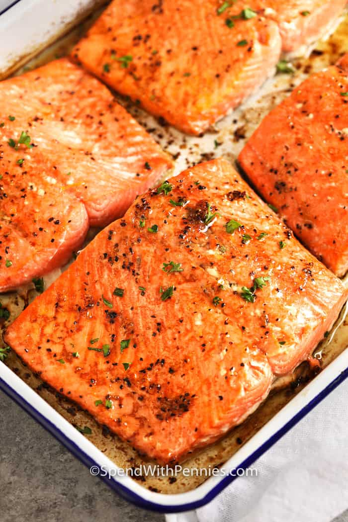 Four salmon fillets baked in a baking dish.