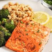 A broiled salmon fillet served with broccoli and rice.