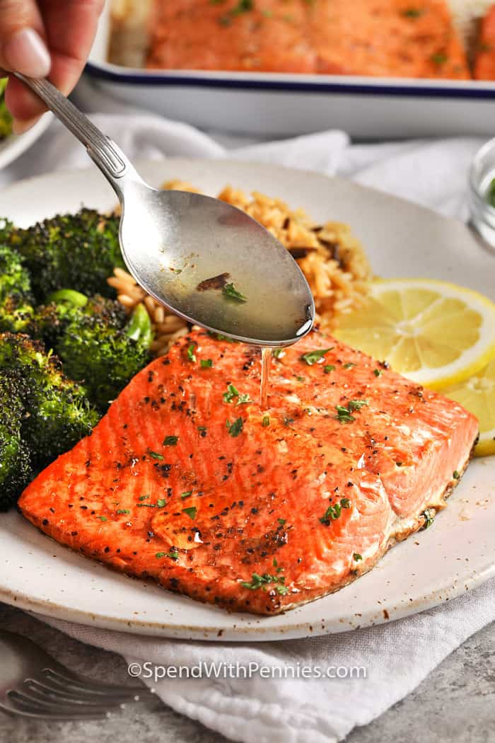 A broiled salmon fillet being drizzled with juices. Served with broccoli and rice.
