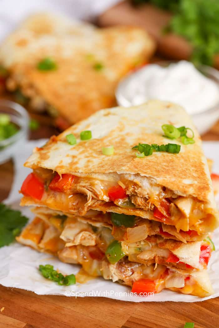 A cutting board sliced chicken quesadilla wedges, salsa, sour cream, and green onions.