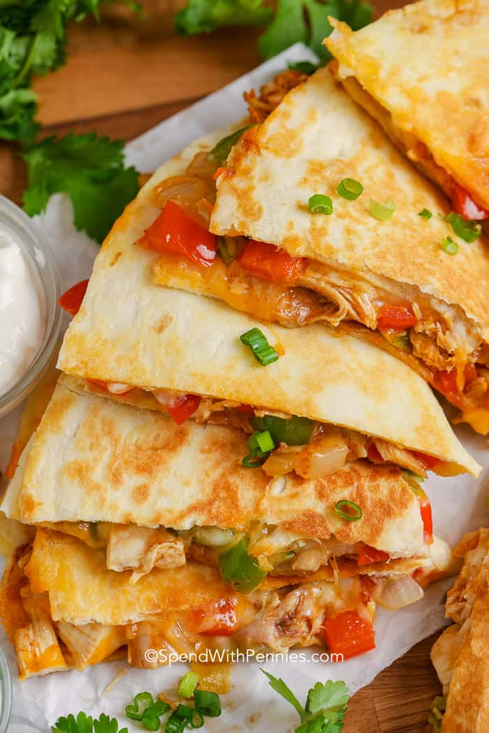 Close up of chicken quesadillas on a baking tray with sour cream and salsa.