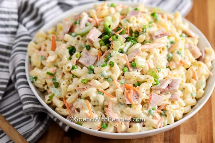 A serving bowl full of creamy macaroni salad, garnished with green onions.