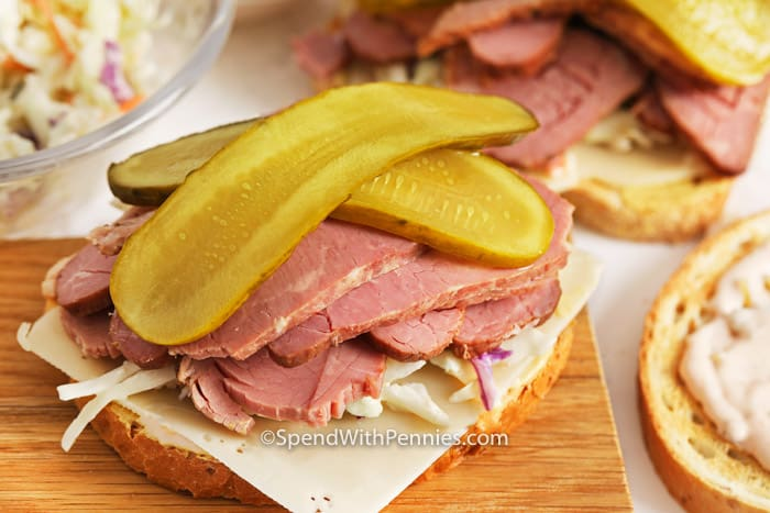 Open Corned Beef Sandwich on a cutting board with pickles