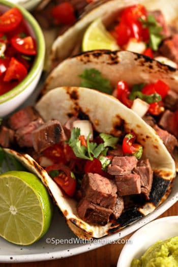 Steak tacos on a plate with limes and tomatoes