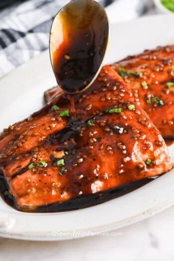 spooning sauce over two honey glazed salmon filets with chives