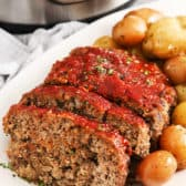 Slices of Instant Pot Meatloaf on a white plate with potatoes