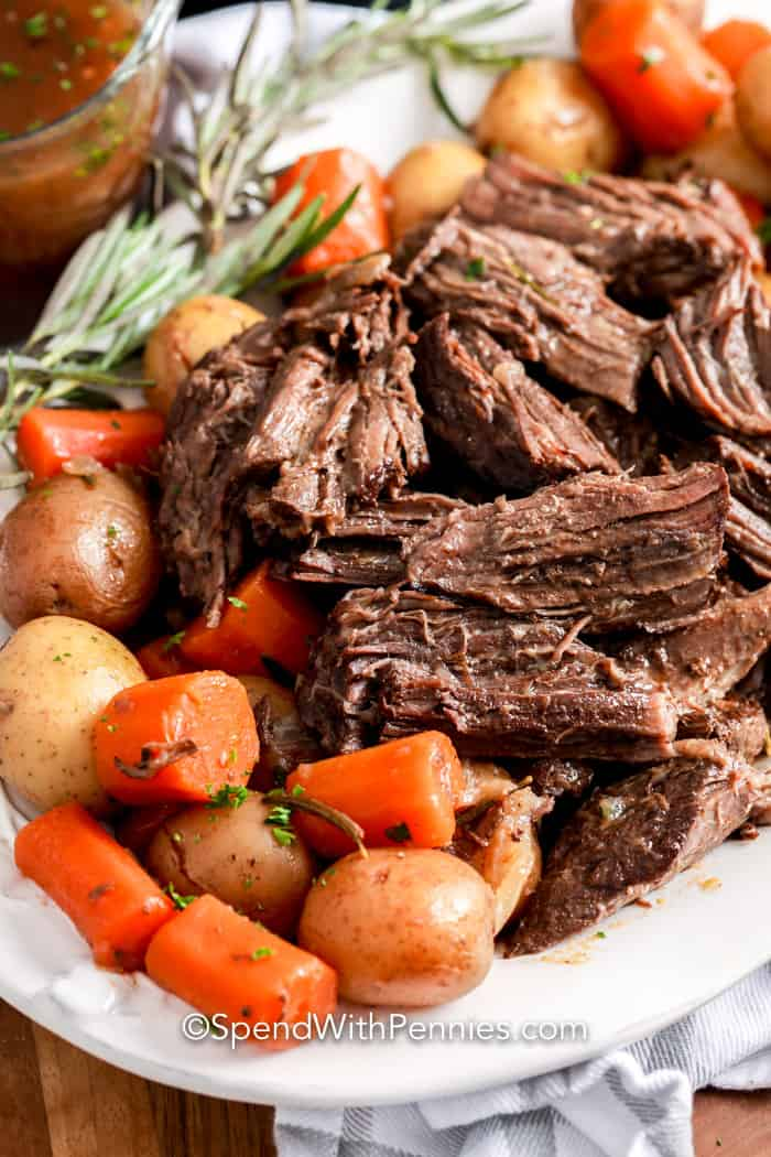 Instant Pot Pot Roast on a plate with veggies and rosemary