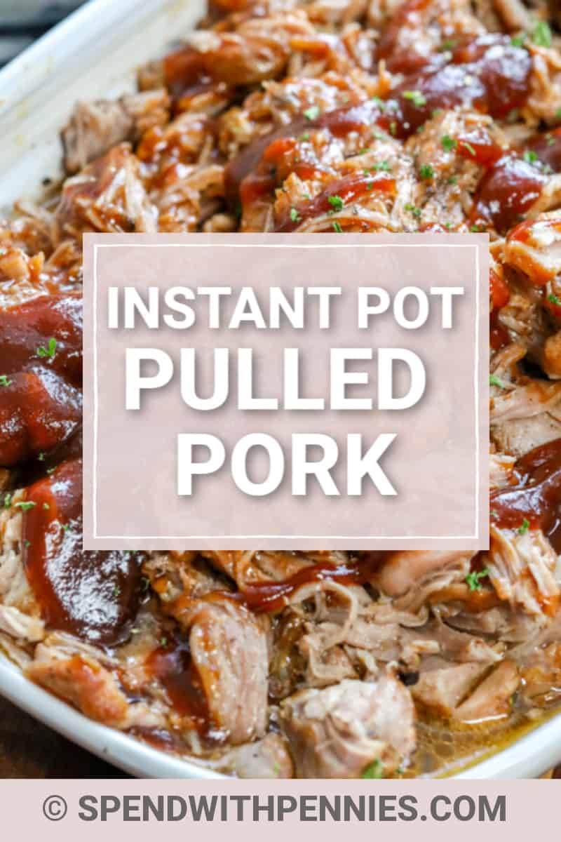 Close up of pulled pork covered in sauce in a white casserole dish.