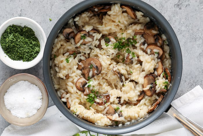 A serving dish of mushroom risotto garnished with parsley and parmesan.