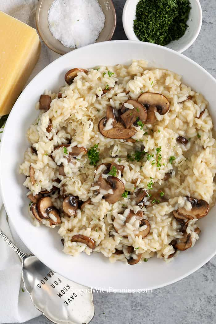A serving dish of mushroom risotto garnished with parmesan and parsley.