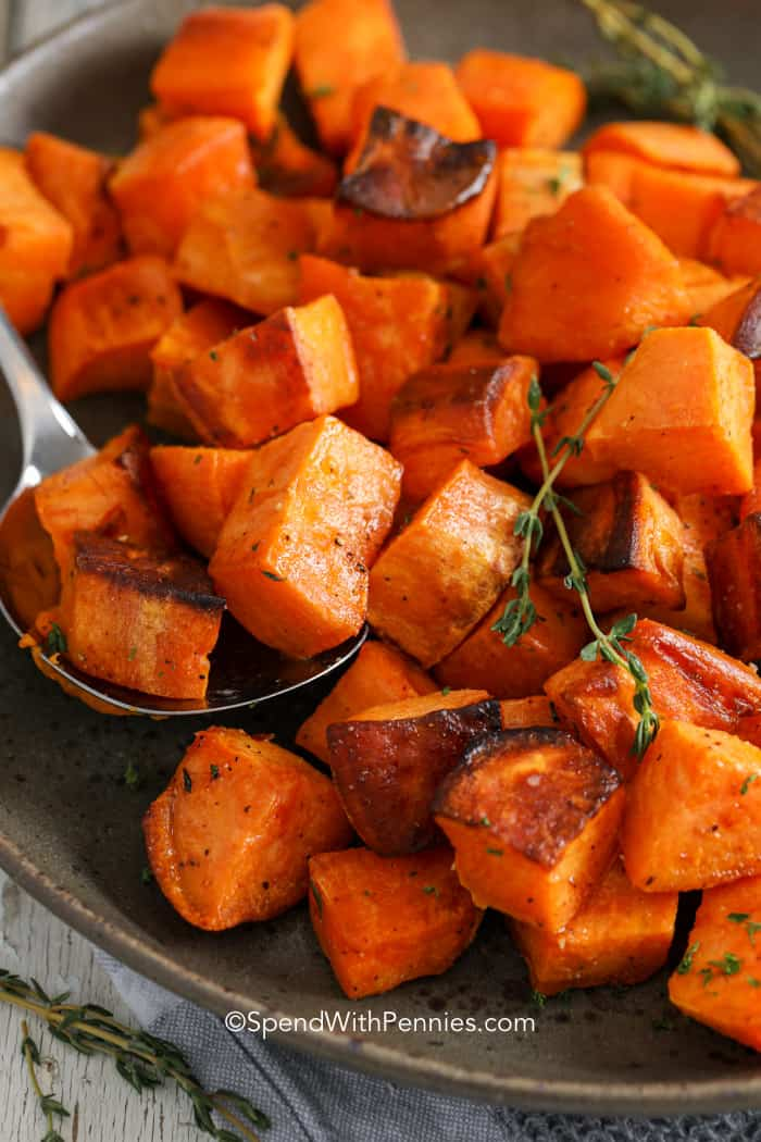 A plate of roasted sweet potatoes with a spoon