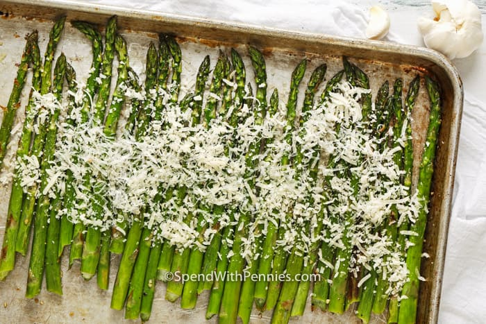 Asparagus spears, topped with parmesan, on a baking sheet.