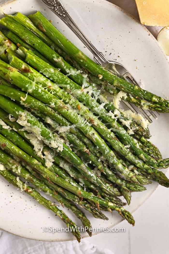 Parmesan roasted asparagus on a plate with a fork.
