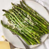 Parmesan roasted asparagus on a serving platter with parmesan and garlic.