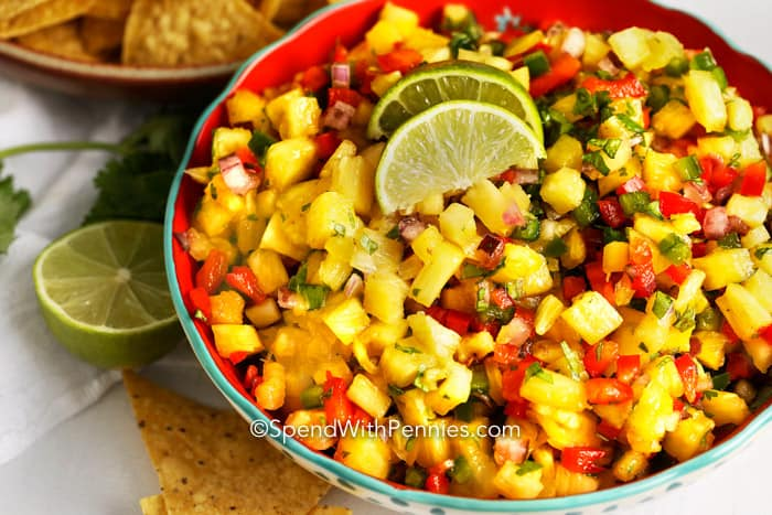 Pineapple salsa topped with 2 lime wedges